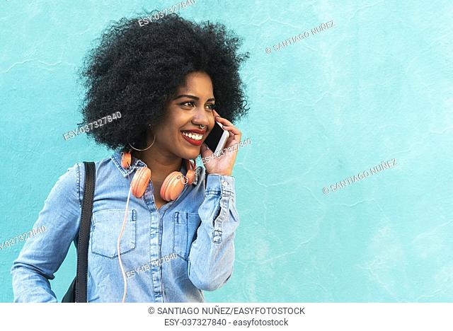 Beautiful afro american woman using mobile in the street. Communication concept