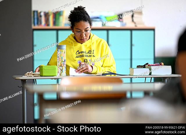 18 May 2020, Baden-Wuerttemberg, Ravensburg: A student at the Albert-Einstein-Gymnasium is looking at Abitur examination assignments