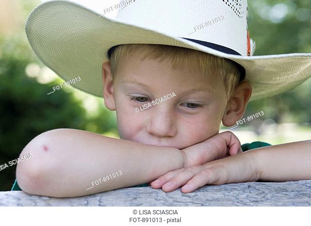 A little boy wearing a cowboy hat looking lonely