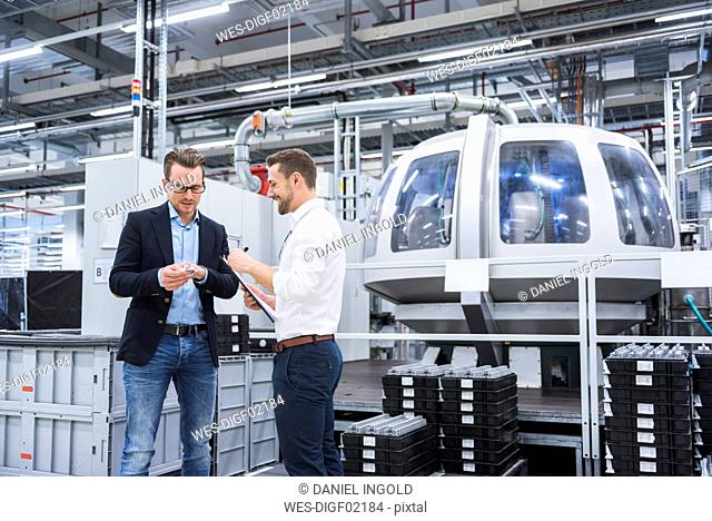 Two men in factory shop floor examining product