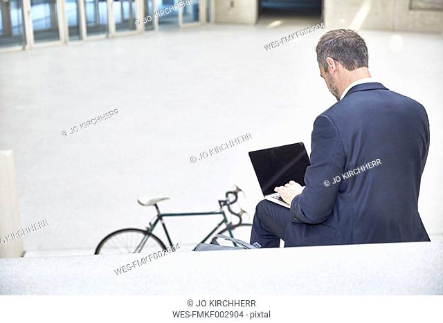 Businesssman on stairs using laptop
