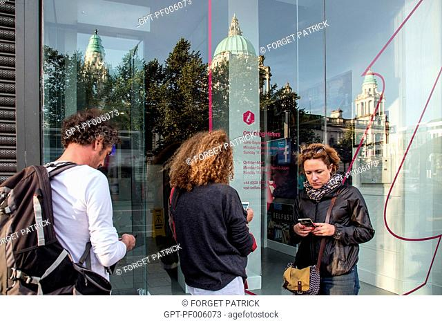 TOURISTS WITH THEIR CELL PHONES TRYING TO GET THE WIFI OF THE TOURIST OFFICE IN FRONT OF THE BELFAST CITY HALL, DONEGALL SQUARE, BELFAST, ULSTER