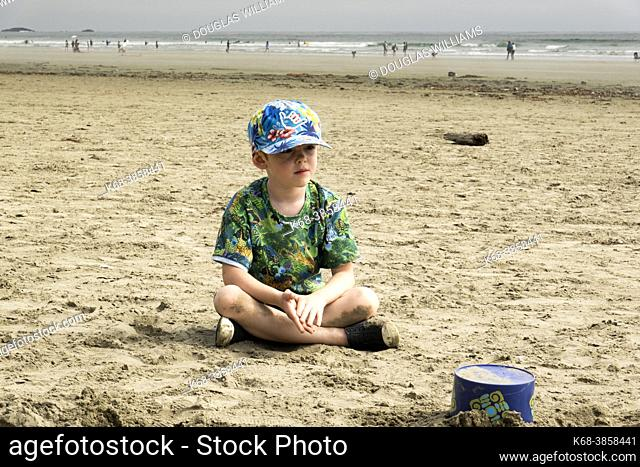 A boy, 7, plays in the sand on the beach near Tofino in Pacific Rim National Park, BC, Canada