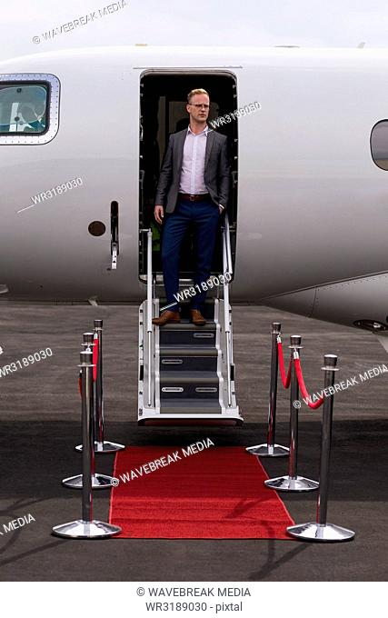 Businessman standing at the entrance of private jet