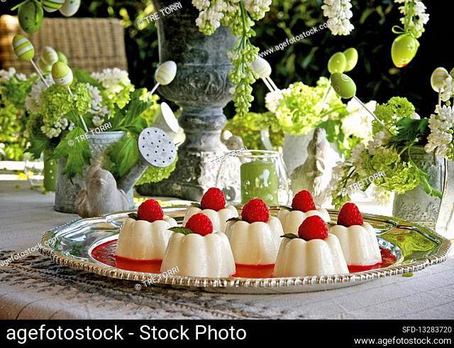Mini panna-cotta with raspberry coulis on a table in a garden