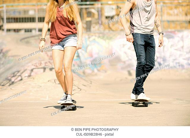 Neck down view of female and male skateboarders skateboarding in skatepark