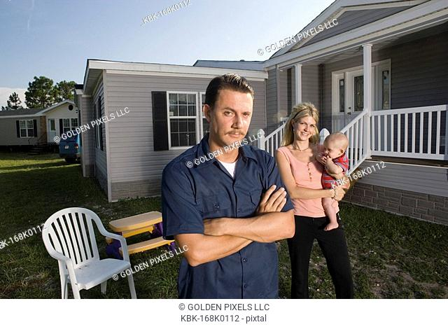 Portrait of a blue-collar man standing in front of a trailer home with wife and baby
