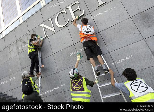 Activists remove letters from the name of the tower, during an action of Extinction Rebellion at the Finance Tower in Brussels, Thursday 25 June 2020