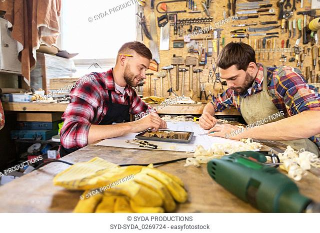 carpenters with tablet and blueprint at workshop