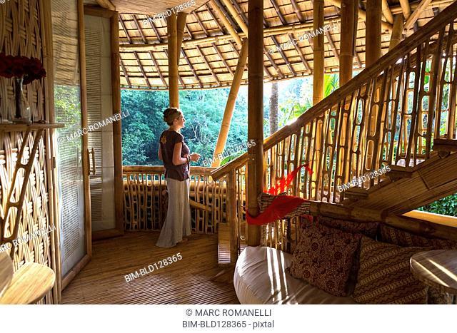 Caucasian woman standing in bamboo room, Ubud, Bali, Indonesia