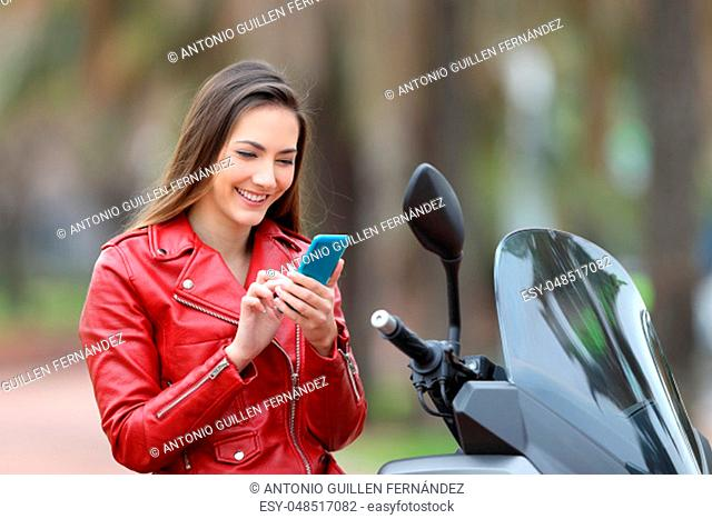 Happy motorbiker using a smart phone sitting on a motorbike
