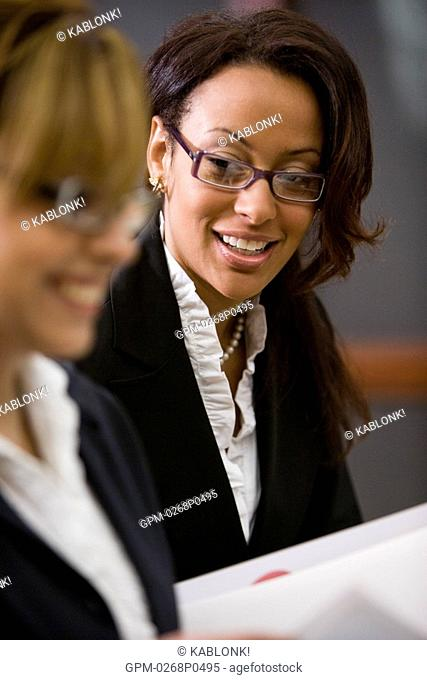 Two multi-ethnic businesswomen working together on notes