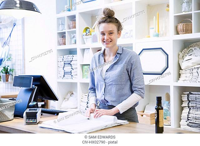 Portrait smiling female cashier wrapping merchandise at checkout counter