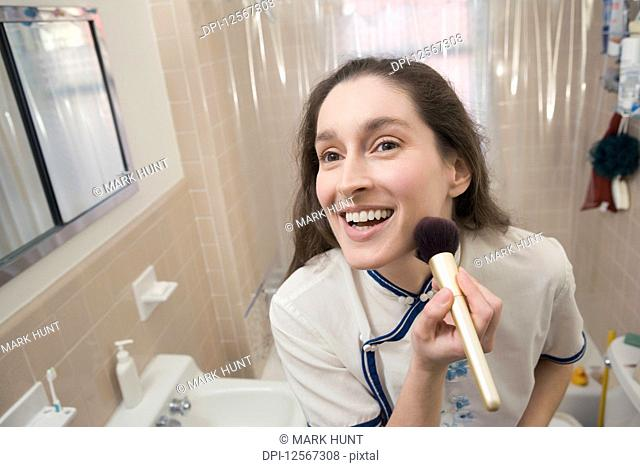 Close-up of a mid adult woman applying make-up on her face and smiling