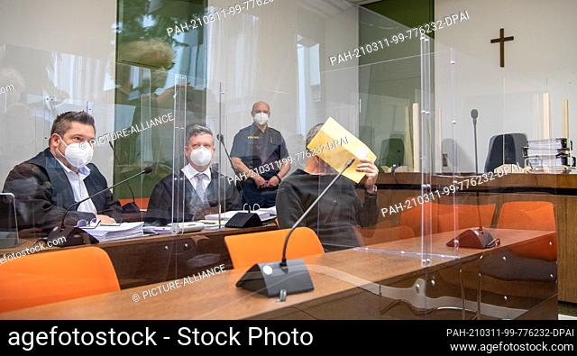 11 March 2021, Bavaria, Munich: The defendant holds an envelope in front of his face at the start of the trial for five counts of attempted murder against him