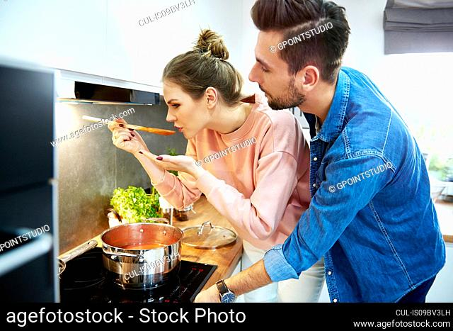Couple tasting tomato soup in kitchen