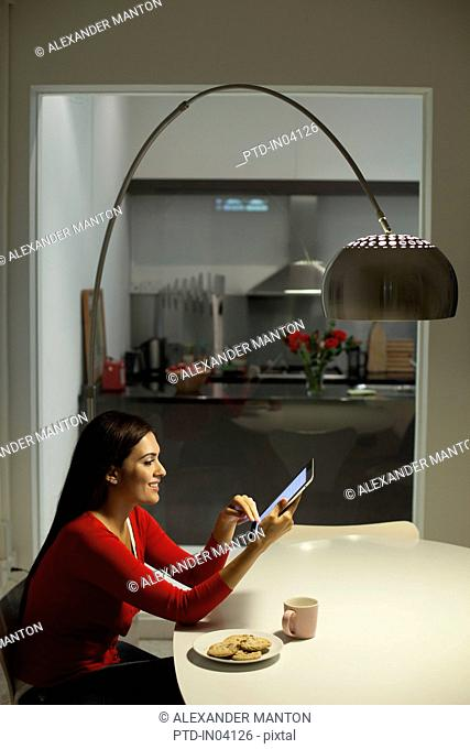 Singapore, Young woman using tablet pc in dining room at night