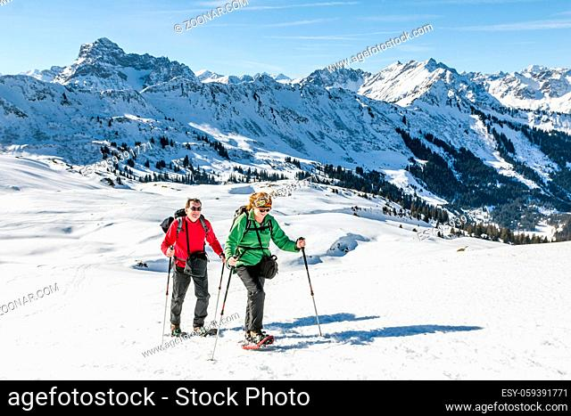Mature couple hiking with snowshoes in winter mountain landscape. Alps, Germany, Bavaria, Allgau