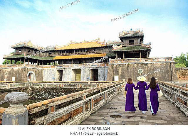 Women in traditional Ao Dai dresses with a paper parasol in the Forbidden Purple City of Hue, UNESCO World Heritage Site, Thua Thien Hue, Vietnam, Indochina