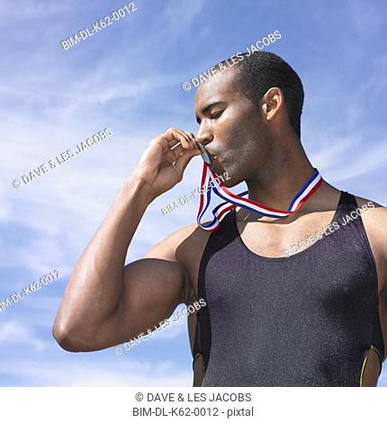 African male athlete kissing medal, Perth, Australia