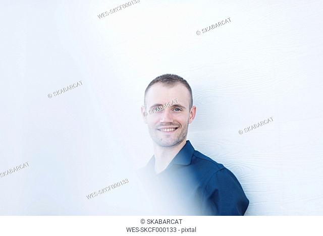 Portrait of smiling businessman in front of white wall