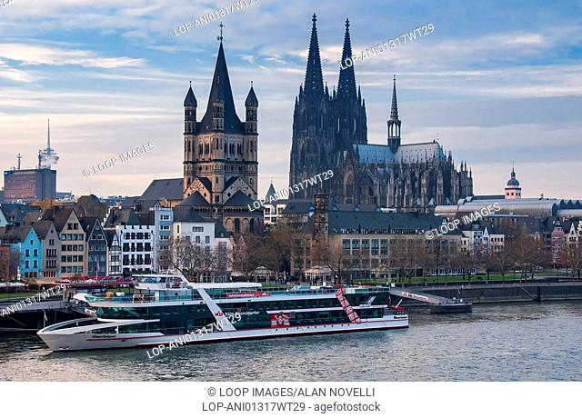 City Hall and Cologne Cathedral tower over a cruise boat on the River Rhine
