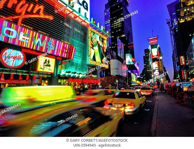 Times Square in New York City at night showing motion blur of taxis