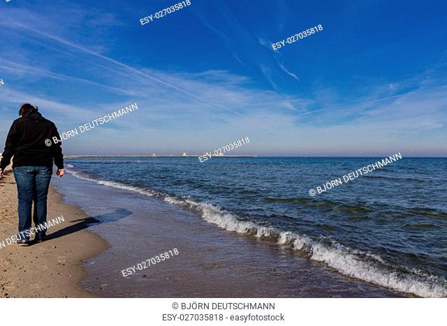 A young woman is walking around at the beach of Kappeln
