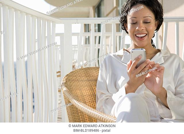 African woman using cell phone on balcony