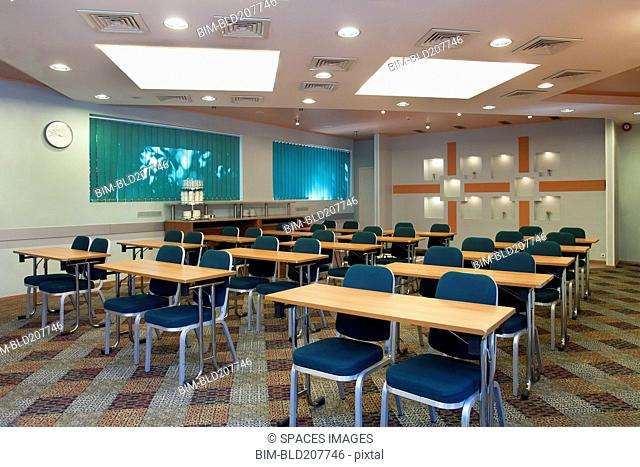 Tables and chairs in empty classroom