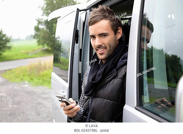 portrait of young man looking out of car window writing text message on mobile phone