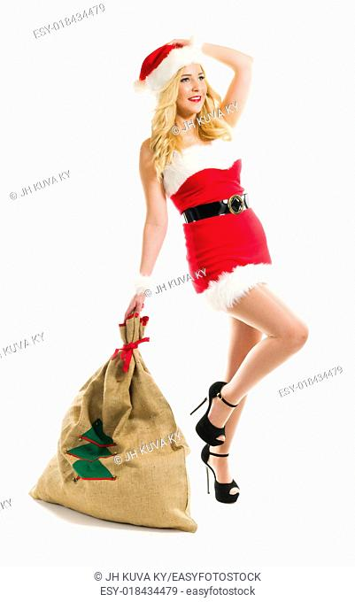 Attractive girl wearing on Santa Claus costume and holds Christmas sack, full length composition and white background