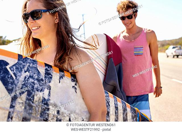 Smiling young couple carrying surfboards on coastal road