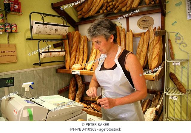Provence - A Brignoles bakery owner selling baguettes at one of the towns bakeries
