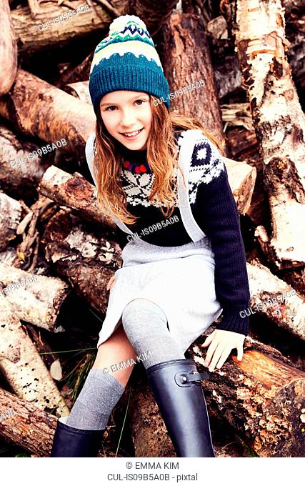 Portrait of young girl, sitting on log pile