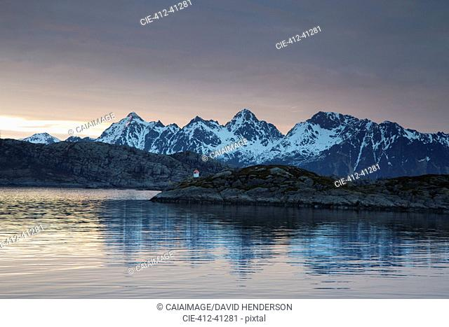 Tranquil view of snowy mountains beyond fjord, Maervoll, Lofoten, Norway