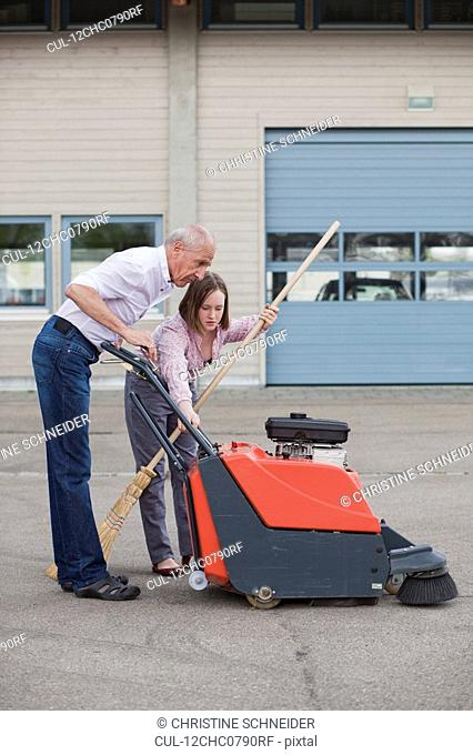 old man and young girl cleaning court