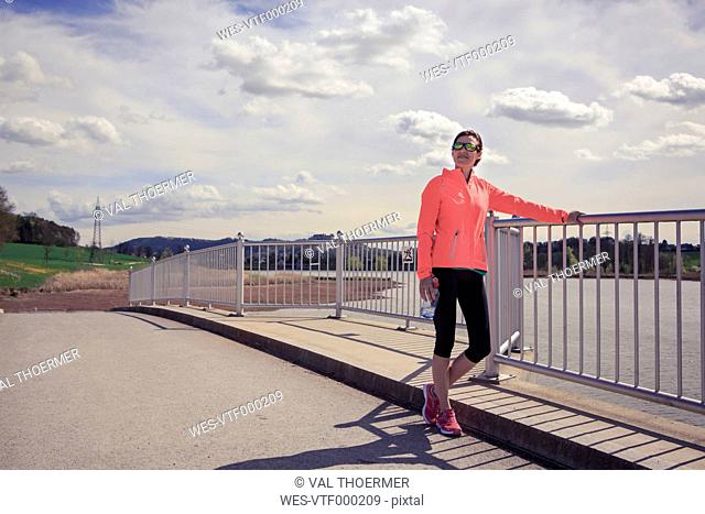Female jogger having a break on a bridge