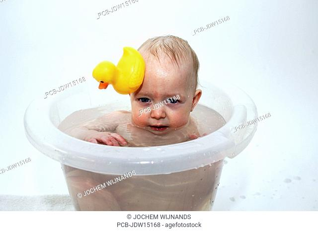 Six month old baby boy in bath tub with rubber duck