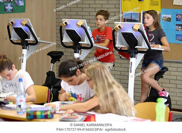 Year five pupils attend a German class while sitting on a bicycle at the Friedrich-Dessauer-Gymnasium (lit. Friedrich Dessau High School) in Aschaffenburg
