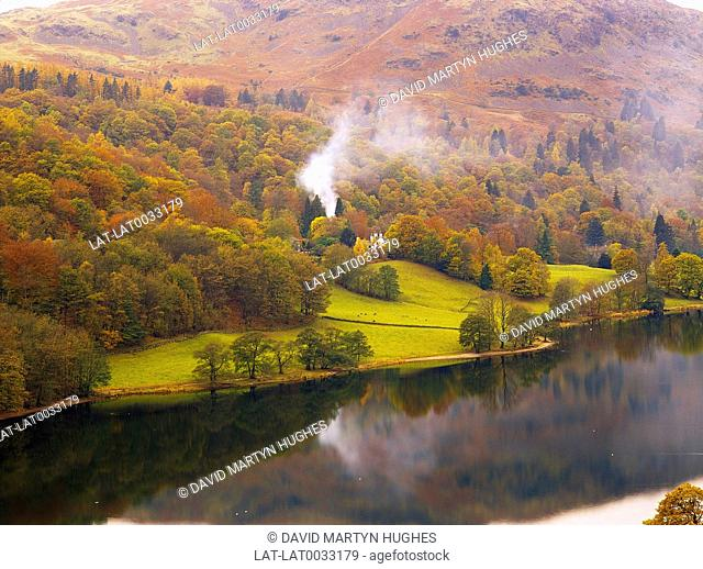 Lake District. View from Loughrigg Terrace. Autumn trees and reflections. Fire smoke. Houses