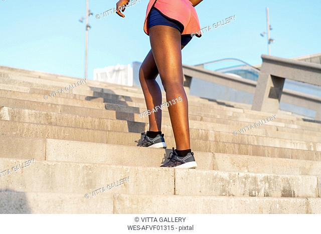 Young woman during workout on stairs, climbing stairs