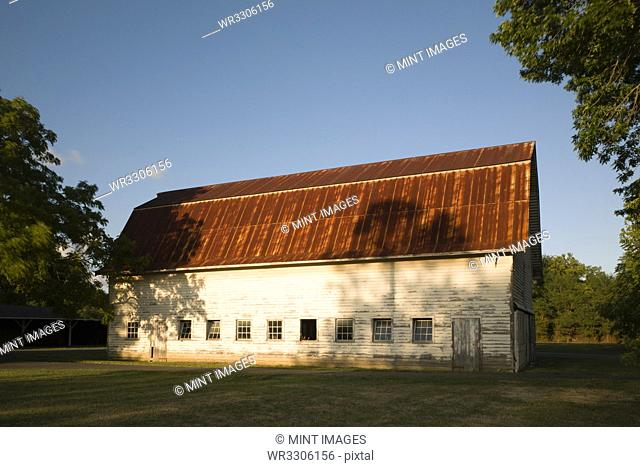 A farm building, red rusty roof and shingle walls, and rows of window set low in the wall