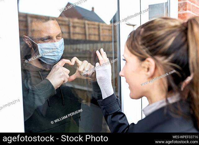 Boyfriend show heart shape gesture to girlfriend through window glass while quarantined at home