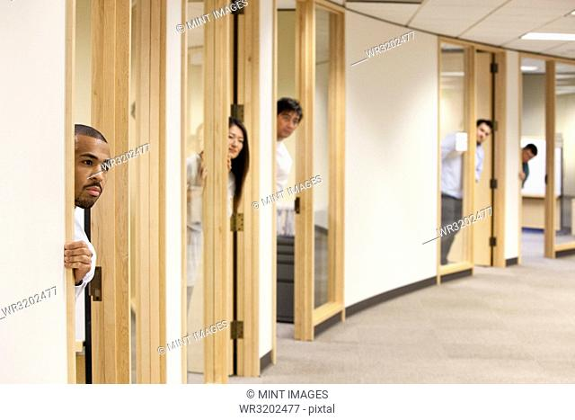 Individual business people looking out the doorway of their offices