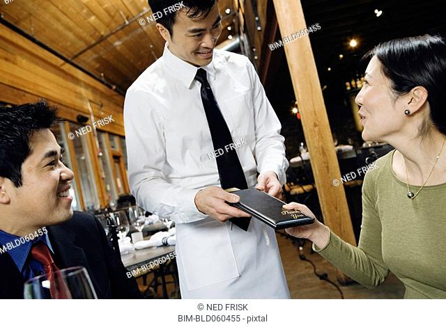 Asian couple paying restaurant bill