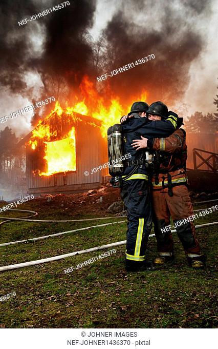 Fire fighters embracing in front of burning buildings
