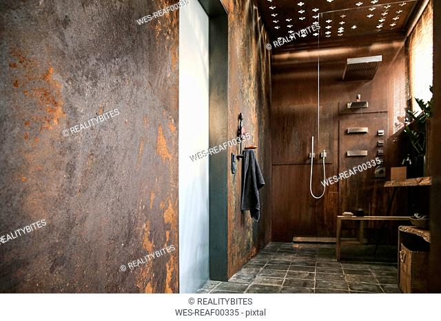 Modern bathroom with corten steel wall cladding and ceiling light effects