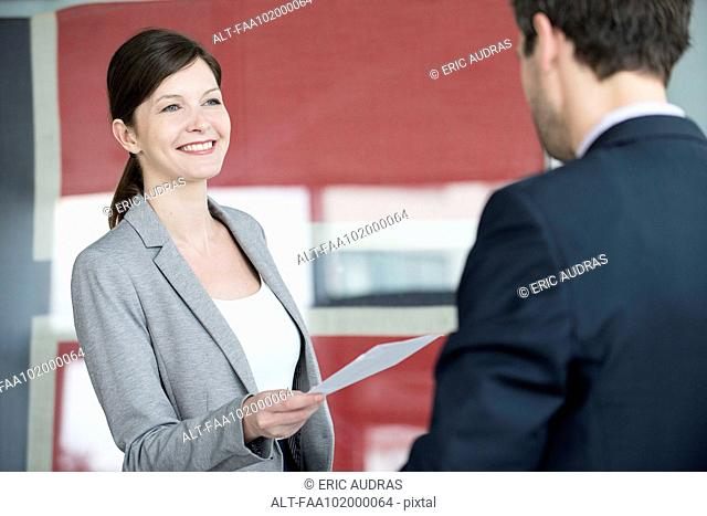 Hotel reception staff delivering fax to guest