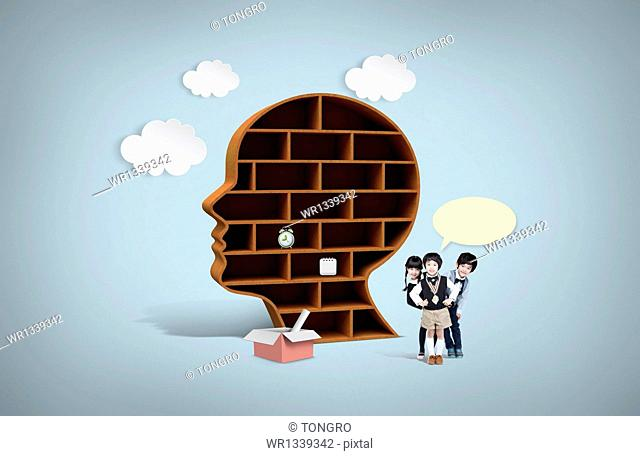 kids standing next to a head shape bookshelf